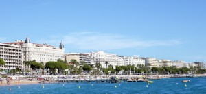 View from the sea of the busy crowded beach and croisette boulevard in Cannes, Cote d'Azur, France with the facade and dome of the famous Carlton International Hotel and various other hotels.